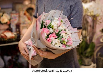 Girl holding a beautiful bouquet of rose colour tulips and white ranunculuses decorating with a green leaves in champagne colour paper