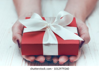 girl holding beautiful  gift for the day valentines day. red box and white bow