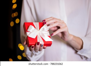girl holding beautiful  gift for the day valentines day. red box and white bow and bokeh in the background