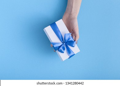 girl holding a beautiful present in hands, women with white gift box with a tied blue ribbon bow in hands on a pastel colored background, top view, concept holiday, love and care
