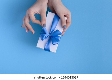 girl holding a beautiful present in hands, women with gift box with a tied blue ribbon bow in hands on a pastel colored background, top view, concept holiday, love and care