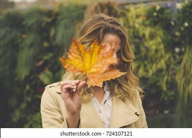 Girl holding big autumn leaf
