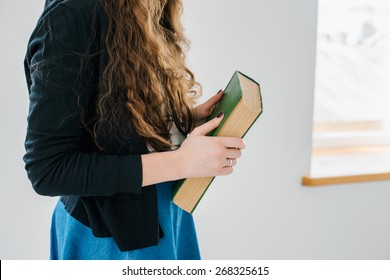 Girl holding a big old green book