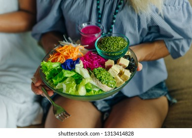 girl holding a big plate of vegan food with salad and sauces