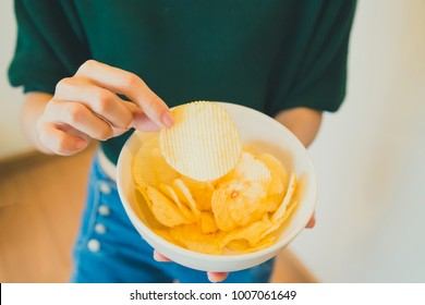 A girl holding the big potato chips bowl. Asking to eating together, Happiness sharing concept.