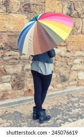 girl holding a big umbrella with color stripes