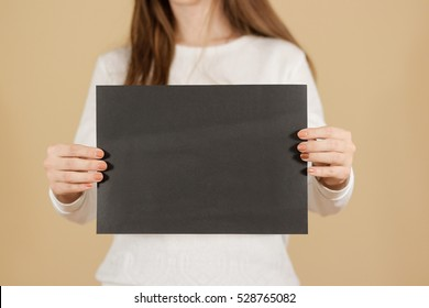 Girl holding black A4 blank paper vertically. Leaflet presentation. Pamphlet hold hands. Woman show clear offset paper. Sheet template. Booklet design sheet display read first person