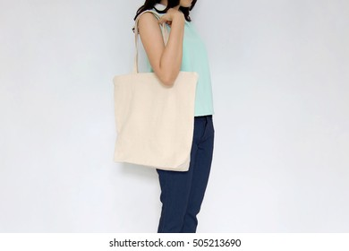 Girl is holding blank canvas bag, design mockup. Handmade shopping tote bag for girls.