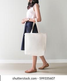 Girl is holding blank canvas tote bag, design mockup. Handmade shopping tote bag for girls.
