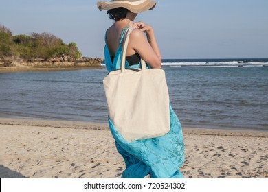 Girl is holding blank canvas tote bag on beach, woman travelling back view