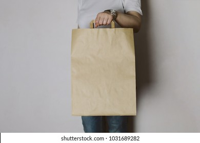 Girl is holding blank craft paper bag, design mockup. Handmade shopping bag for gift or food.