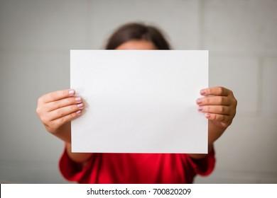 Une fille tenant un papier vierge