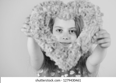 Girl holding blurred pink heart on blue background. Valentine and valentines day celebration. Sweetheart child with long hair in red dress. Kindness and tenderness. Romantic love concept.