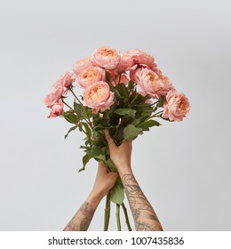 the girl is holding a bouquet of fresh pink roses,