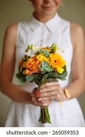 girl holding a bouquet of orange flowers in rustic style