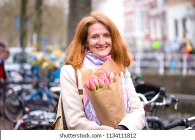 girl holding a bouquet of tulips standing on a street of Amsterdam