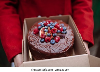 girl holding a box of chocolate cake with berries