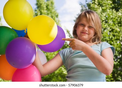 Girl holding bunch of balloons