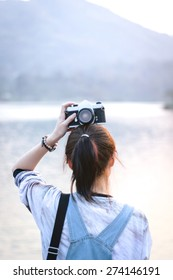 A girl holding camera over her head