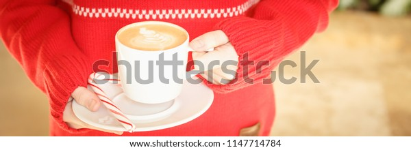 Girl holding a cappuccino cup with candy cane. Concept of Christmas holiday. Holiday background. Warm tone. Horizontal, wide screen banner format