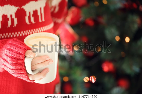 Girl holding a cappuccino cup. Concept of Christmas holiday. Holiday background. Warm tone. Horizontal