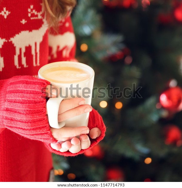 Girl holding a cappuccino cup. Concept of Christmas holiday. Holiday background. Warm tone. Square