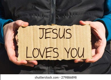 Girl holding a carton paper with text Jesus loves you