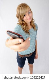 Girl Holding Cellphone. Thirteen year old girl holding her cellphone toward the viewer. Focus on model. Note: Not Isolated.