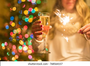 Girl holding champange glass and sparkler at holiday celebration