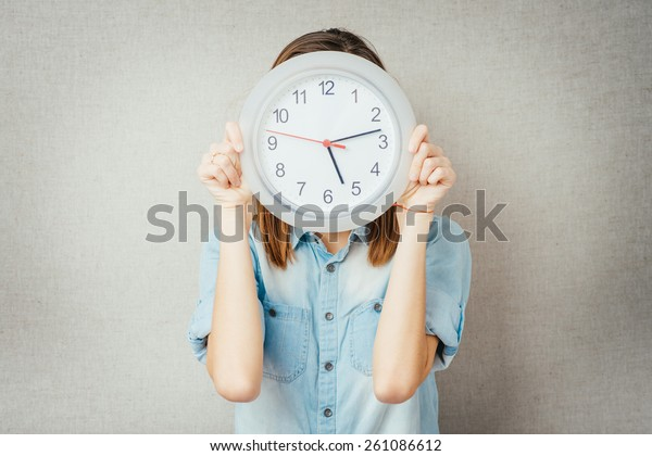 girl holding a clock