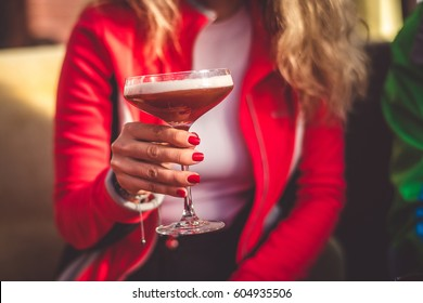 A girl holding a cocktail in her hand