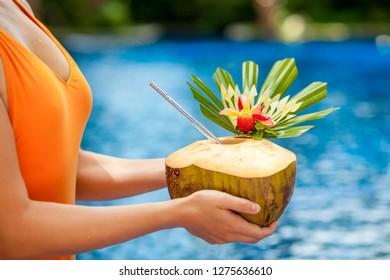 Girl holding a coconut hands closeup