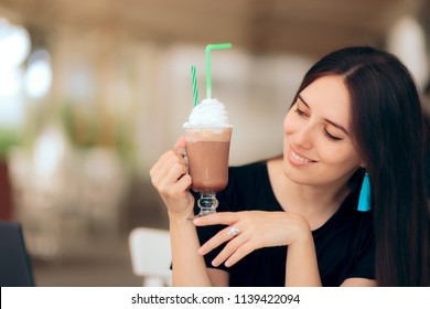 Girl Holding Coffee Drink with Whipped Cream on Top. Woman drinking hot chocolate at a restaurant