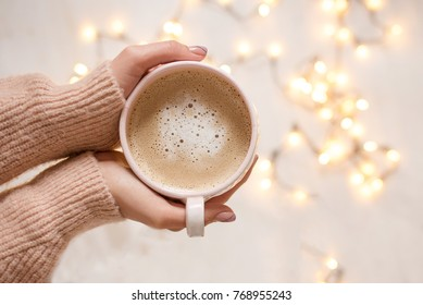 Girl holding coffee in hands over light bokeh background. Overhead shot.