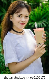 girl holding a cold drink milk tea and smiling