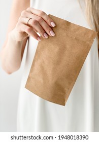 girl holding a craft package with tea or coffee in her hands on a white background