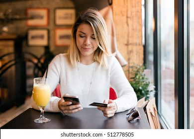 Girl holding credit card and texting.