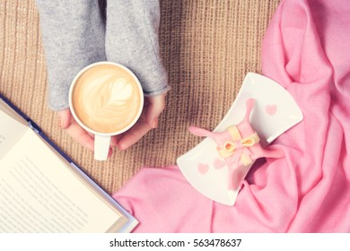 Girl holding cup of coffee with latte art. Pink textile, gift style cake, open book. Valentines day and leisure time concept. Pastel colors, warm toning. Horizontal, top view