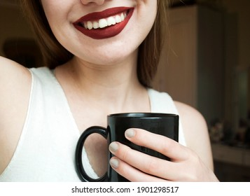 The girl is holding a cup and smiling. Beautiful smile, white teeth and red lipstick.