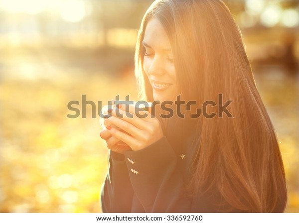 a girl holding a cup of warm tea, autumn leaves