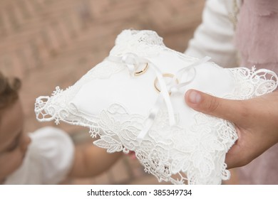 a girl is holding a cushion with wedding rings