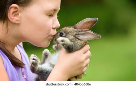 Girl is holding a cute little rabbit, outdoor shoot