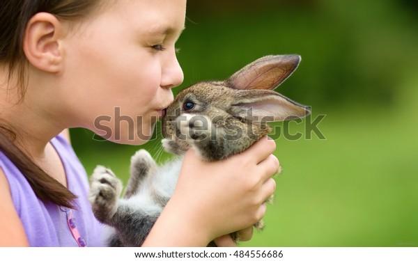 Girl is holding a cute little rabbit, outdoor shoot