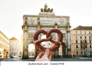 The girl is holding a delicious traditional German pretzel in the hand against the backdrop of the Victory Gate triumphal arch Siegestor in Munich. Germany