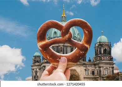 The girl is holding a delicious traditional German pretzel in the hand against the backdrop of the Berlin Cathedral is called Berliner Dom. Berlin, Germany