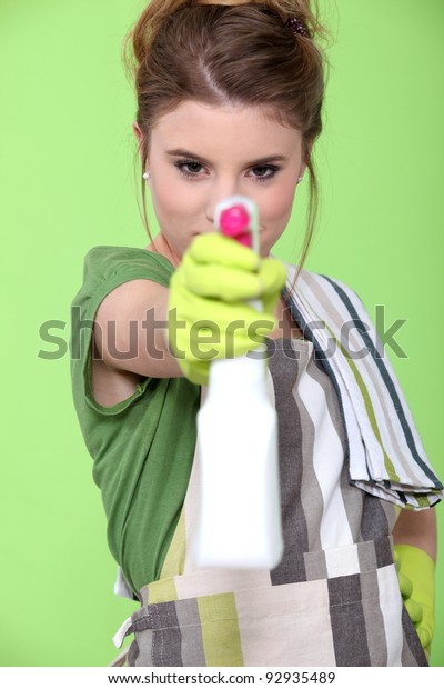 girl holding detergent with pistol pump against green background
