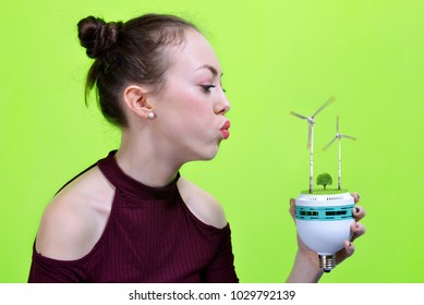 Girl holding eco LED bulb with wind turbines in hand on green background.The concept alternative energy.