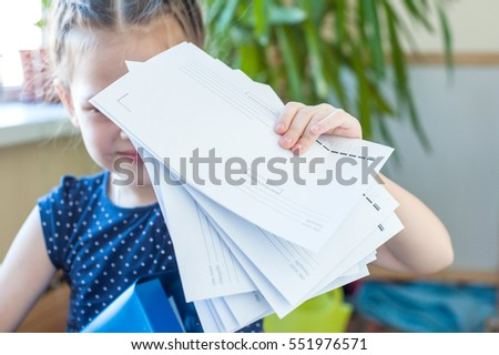 A girl holding a lot of empty white envelopes