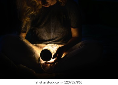 Girl holding a fireflies jar with lights on it. She is looking down at it. Only a part of her body is iluminated.