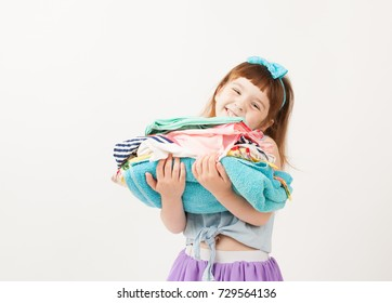 Girl holding folded clothes in his hands on white background. An empty space to insert text.